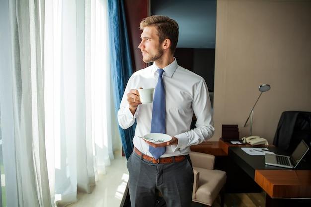 Podróż służbowa i koncepcja ludzi - biznesmen picia kawy w pokoju hotelowym