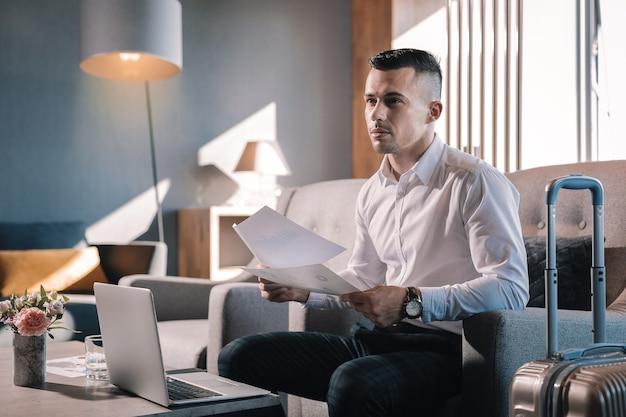 Podróż służbowa. przystojny biznesmen sukcesu siedzi w holu hotelu mając podróż służbową