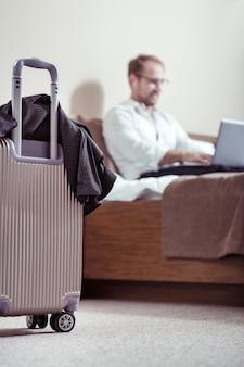 Podróż służbowa. selektywne skupienie walizki stojącej na podłodze z miłym, przyjemnym człowiekiem pracującym