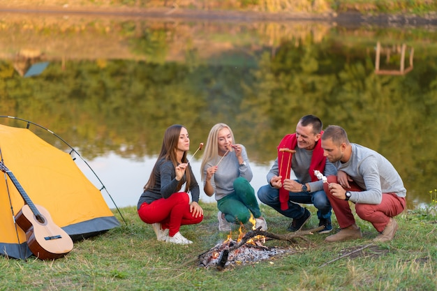 Podróż, turystyka, podwyżka, pinkin i ludzie pojęć, - grupa szczęśliwi przyjaciele smaży kiełbasy na ognisku blisko jeziora.