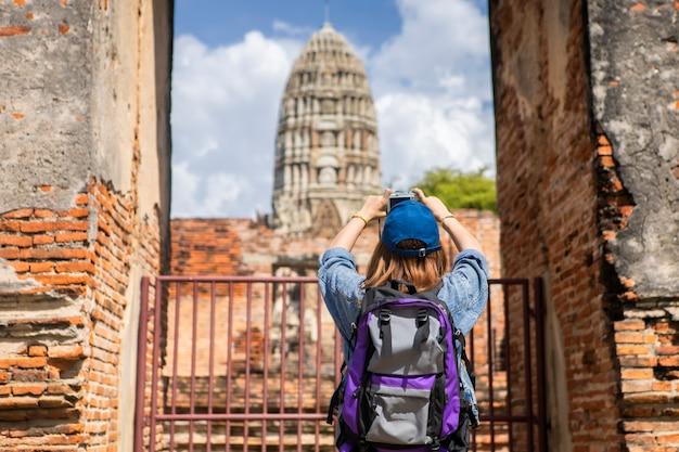 Podróż w tajlandii, świątynia ayutthaya. turystyczne azjatyckie kobiety trzyma kamerę z niesie plecaka.