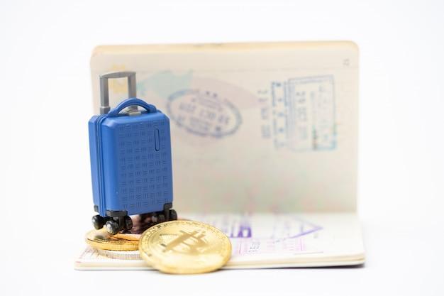 Podróże i oszczędności finansowe. miniaturowy bagaż i model monety bitowej na paszporcie. płacenie z koncepcją monety bitowej.