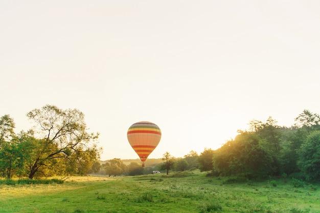 Podróże i sport. wielo- barwiony pasiasty gorące powietrze balonu latanie nad dolina w niebie przy wschodem słońca.