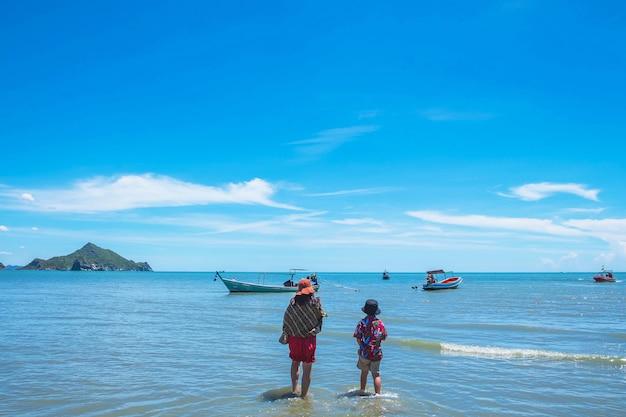 Podróże matki i dziecka idą do łodzi na morzu na wakacjach w lecie