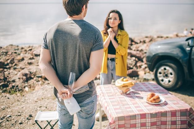 Podróże, turystyka - piknik nad wodą. para idzie na przygodę. koncepcja podróży samochodem. mężczyzna i kobieta piją szampana.