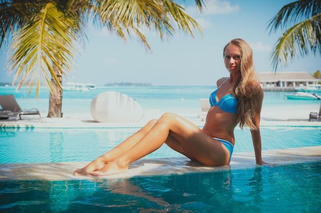 Podróże wakacje - piękna młoda ładna blondynka z powrotem w bikini na jej doskonałe ciało sexy sport relaks w basenie w pobliżu rajskiej plaży na tropikalnej plaży na karaibach w słoneczny dzień w hotelu