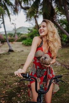 Podróżna blondynki piękna kobieta z kokosem jedzie na rowerze w tropikalnym dżungla parku. podróż przygody natura w chinach, turystyczny piękny cel azja, letnie wakacje wakacje podróż wycieczka koncepcja
