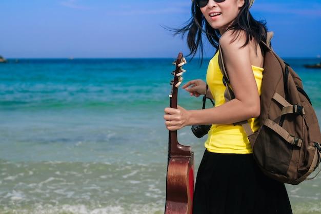 Podróżna kobieta ma torbę i gitarę stojącą na plaży