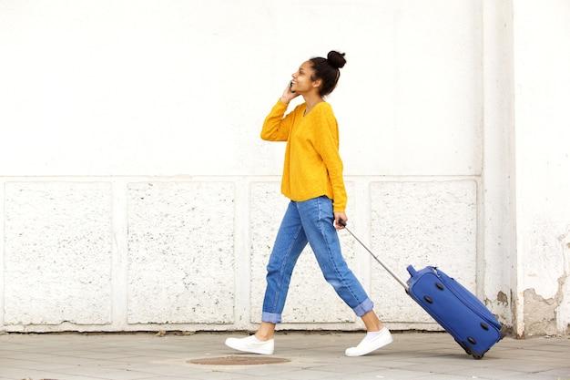 Podróżna kobieta opowiada na telefonie komórkowym