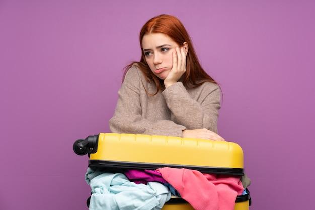 Podróżna kobieta z walizką pełną ubrań