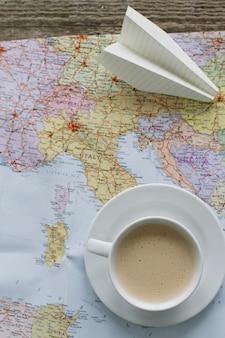 Podróżna mapa, papierowy samolot i filiżanka kawy