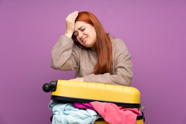 Podróżna młoda kobieta z walizką pełną ubrań, mająca wątpliwości z mylącym wyrazem twarzy
