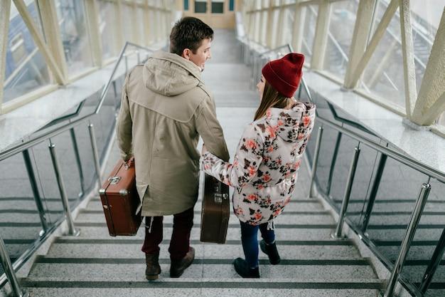 Podróżna para z torbami chodzi w dół schodki.