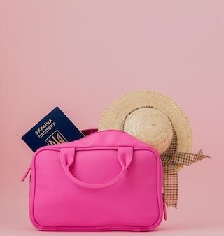 Podróżna różowa walizka i dokument paszportowy, torebka na różowo, koncepcja podróży i podróży.
