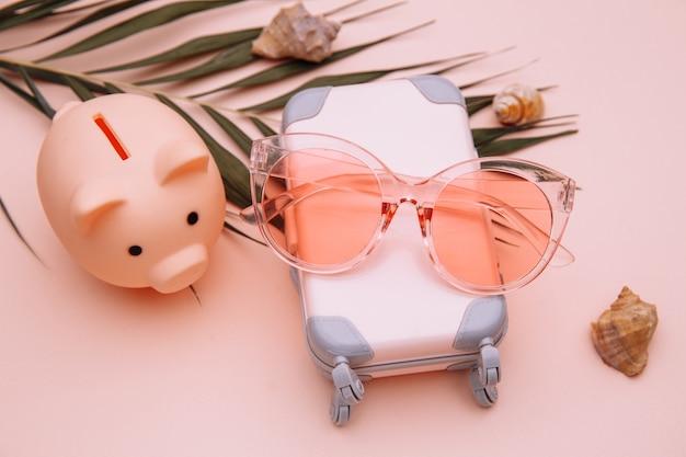 Podróżna walizka bagażowa ze skarbonką na różowym stole
