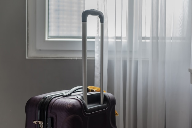Podróżna walizka na podłoga z zasłoną w tle.