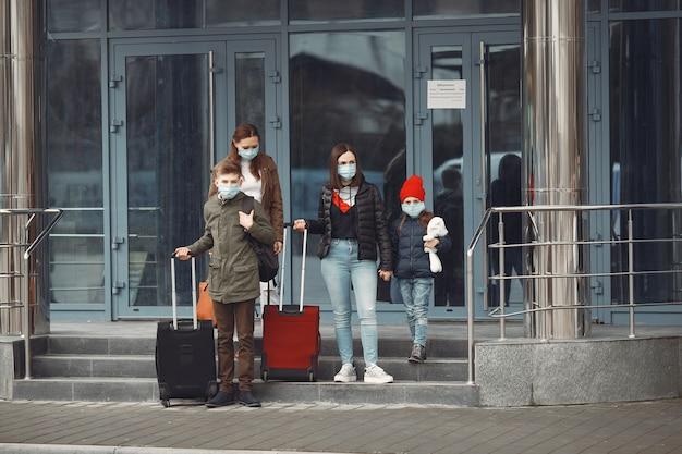 Podróżni opuszczający lotnisko mają na sobie maski ochronne