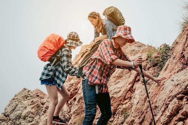 Podróżni używają kijków trekkingowych, aby schodzić ze szczytu góry.pomocna dłoń
