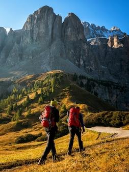 Podróżni wędrują zapierającym dech w piersiach krajobrazem dolomitów