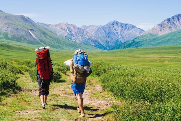 Podróżni z dużymi plecakami idą ścieżką w zielonej dolinie do wspaniałych gigantycznych gór