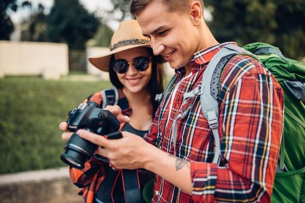 Podróżni z plecakiem oglądają zrobione zdjęcia