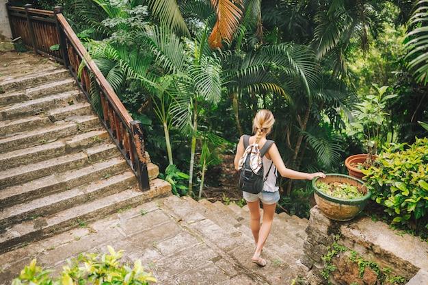 Podróżnicza blondynki backpacker kobieta chodzi i odkrywa dżungla tropikalnego parka, podróżuje przygodę natura w chinach, turystyczny piękny cel azja, letnie wakacje wakacje podróż wycieczka koncepcja