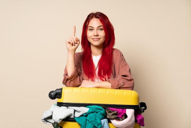 Podróżnicza dziewczyna z walizką pełną ubrań na beżu skierowaną w górę świetny pomysł