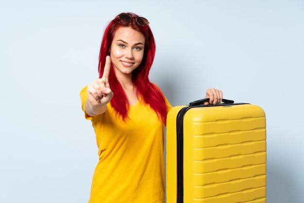 Podróżnicza kobieta trzyma walizkę odizolowywająca na błękit ścianie pokazuje palec i podnosi