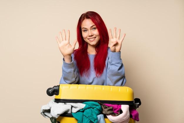 Podróżnicza kobieta z walizką pełną ubrań odizolowywających na beżowej ścianie liczy dziewięć z palcami