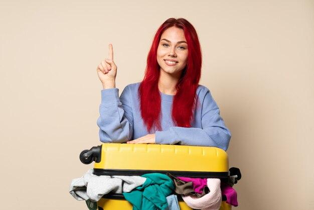 Podróżnicza kobieta z walizką pełną ubrań odizolowywających na beżowej ścianie pokazuje i podnosi palec w znaku najlepszy