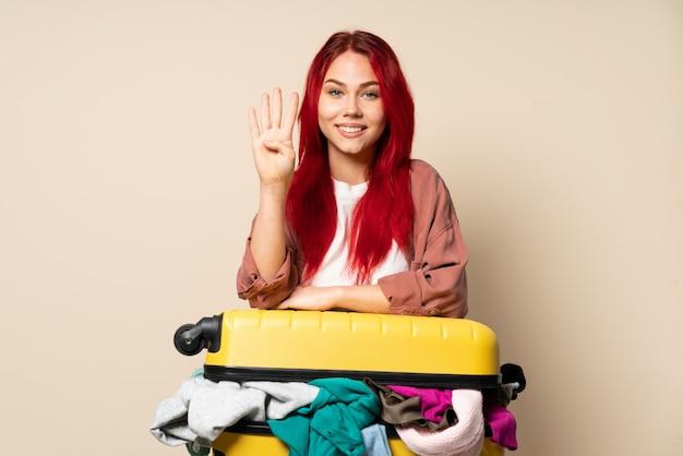 Podróżnicza kobieta z walizką pełną ubrań odizolowywających na beżowej ścianie szczęśliwa i liczy cztery z palcami