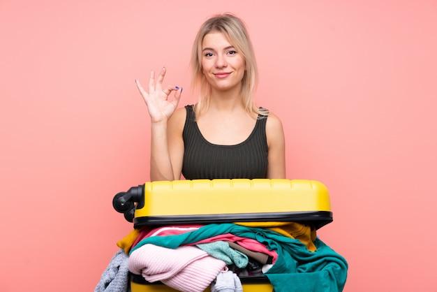 Podróżnicza kobieta z walizką pełną ubrania pokazuje ok znaka palcami