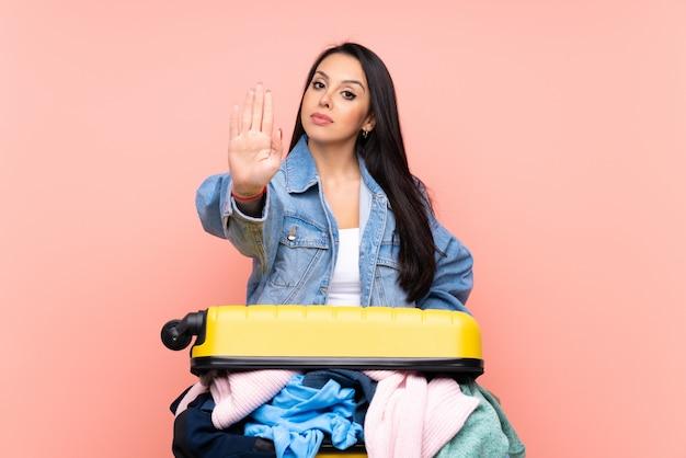 Podróżnicza kolumbijska dziewczyna z walizką pełną ubrań na różowej ścianie robi gest ręką