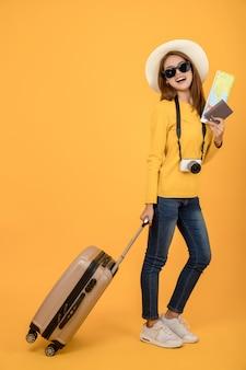Podróżnicza turystyczna kobieta w lat przypadkowych ubraniach odizolowywających nad żółtym tłem