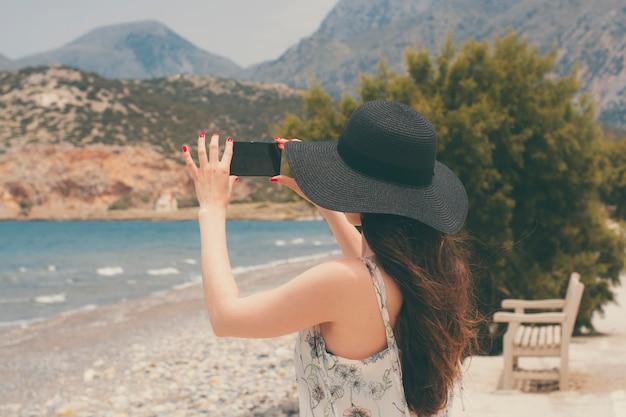 Podróżniczka fotografująca na smartfonie piękne naturalne widoki na morze i góry na krecie.