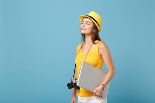 Podróżniczka turystyczna kobieta w żółtych letnich ubraniach, kapeluszu z laptopem na niebiesko