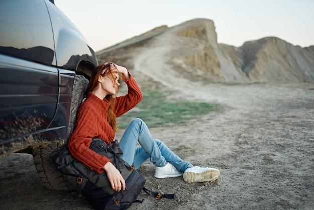 Podróżniczka w swetrze i dżinsach siedzi na ziemi z plecakiem w dłoni w pobliżu samochodu