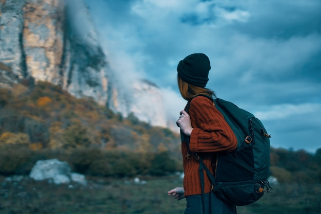 Podróżniczka w swetrze z plecakiem na plecach turystyka chmury niebo krajobraz