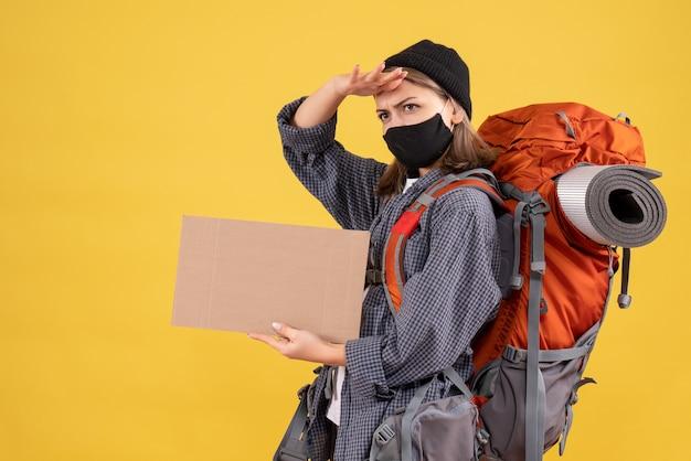 Podróżniczka z czarną maską i plecakiem trzymająca kartonowe obserwacje
