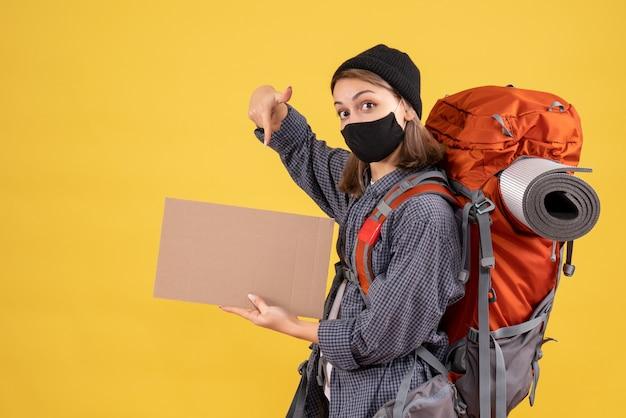 Podróżniczka z czarną maską i plecakiem wskazująca na karton