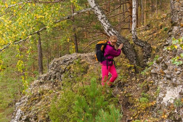 Podróżniczka z plecakiem ostrożnie pokonuje górski szlak wśród jesiennego lasu