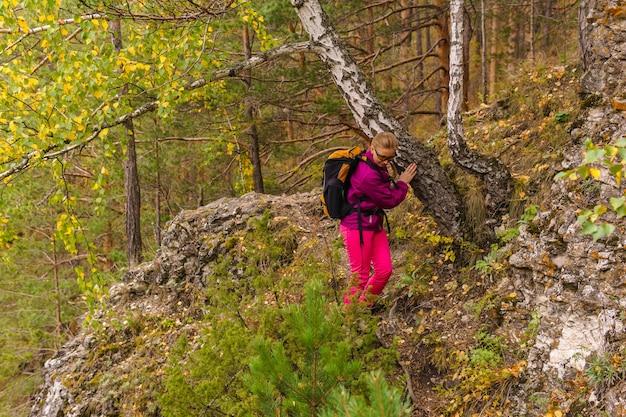 Podróżniczka z plecakiem pokonuje górski szlak wśród jesiennego lasu