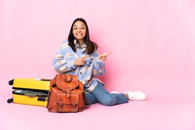 Podróżniczka z walizką siedząca na podłodze przestraszona i wskazująca w bok