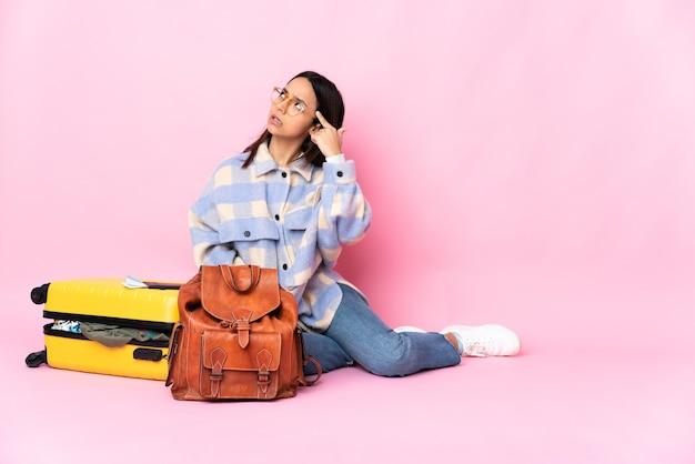 Podróżniczka z walizką siedząca na podłodze w geście szaleństwa kładzie palec na głowie