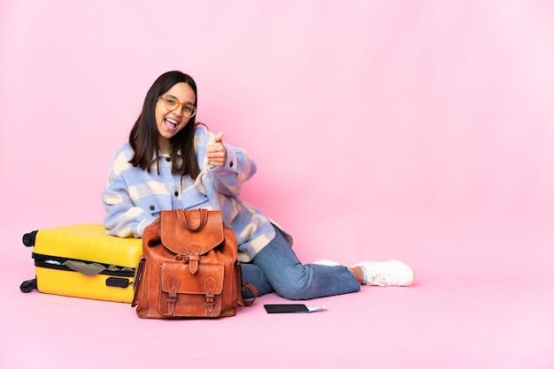 Podróżniczka z walizką siedząca na podłodze z podniesionymi kciukami, ponieważ wydarzyło się coś dobrego