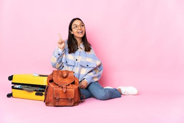 Podróżniczka z walizką siedząca na podłodze, zamierzająca znaleźć rozwiązanie, podnosząc palec do góry