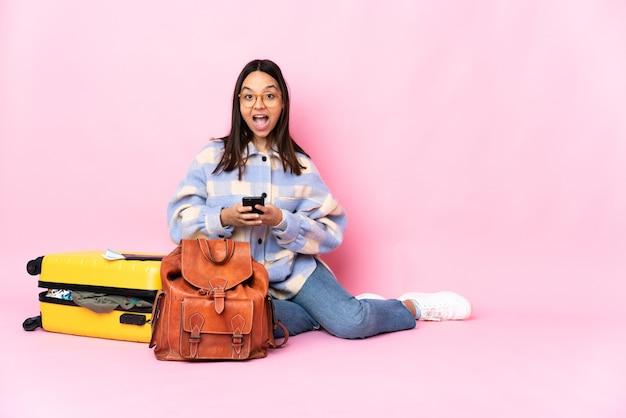 Podróżniczka z walizką siedząca na podłodze zaskoczona i wysyłająca wiadomość