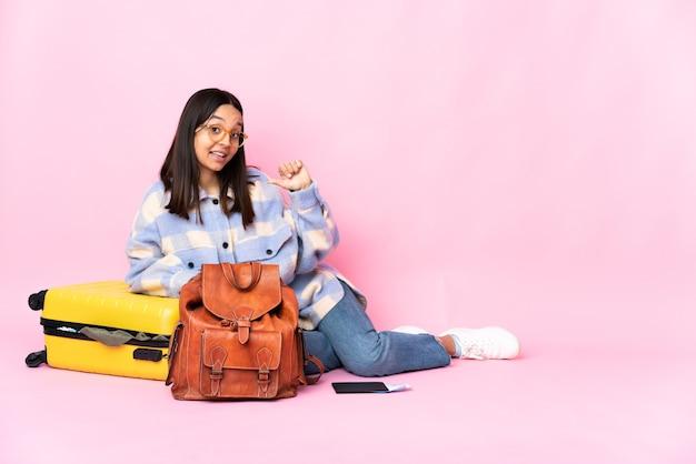 Podróżniczka z walizką siedzi na podłodze dumna i zadowolona z siebie