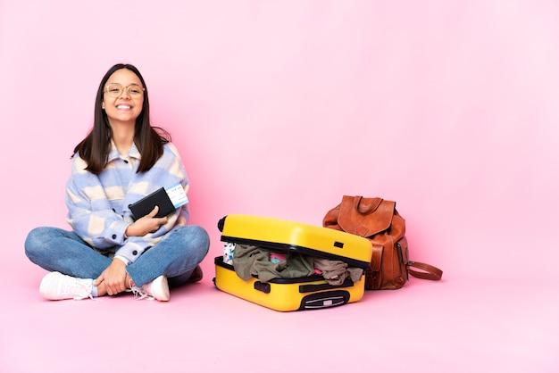 Podróżniczka z walizką siedzi na podłodze, trzymając ręce skrzyżowane w pozycji czołowej