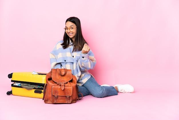 Podróżniczka z walizką siedzi na podłodze, zapraszając do przyjścia z ręką